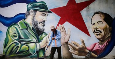 TOPSHOT - A municipal worker sweeps the floor in front of a mural depicting Cuban revolutionary leader Fidel Castro (L) and Nicaraguan President Daniel Ortega at Cuba square in Managua on November 26, 2016, the day after Castro died.   Cuban revolutionary leader Fidel Castro has died aged 90, prompting mixed grief and joy Saturday along with international tributes for the man whose iron-fisted rule defied the United States for half a century. / AFP PHOTO / INTI OCONINTI OCON/AFP/Getty Images
