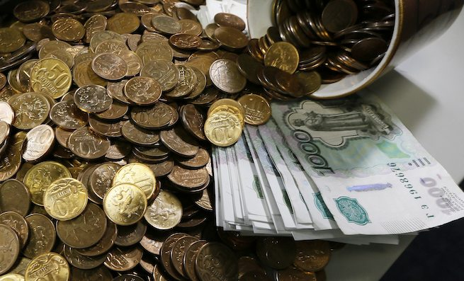 Russian 1000-rouble banknotes, 50 and 10 kopeck coins are seen on a table at a private company's office in Krasnoyarsk, Siberia November 6, 2014. The rouble briefly weakened to a new all-time low of over 46 roubles per dollar on the Moscow Exchange on Thursday, extending losses from earlier in the session to trade over 2 percent lower than the previous close. REUTERS/Ilya Naymushin (RUSSIA - Tags: BUSINESS)